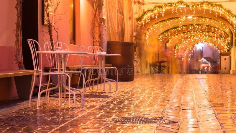 Café de rue la nuit contre des lumières d'illumination de ville images stock
