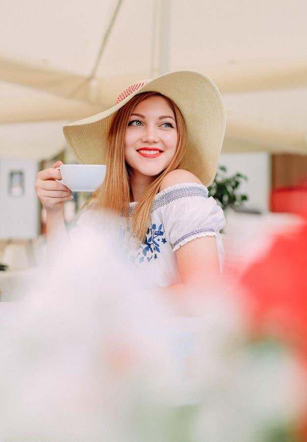 Café de sourire de cappuccino de chapeau de fille en dehors de terrasse image stock