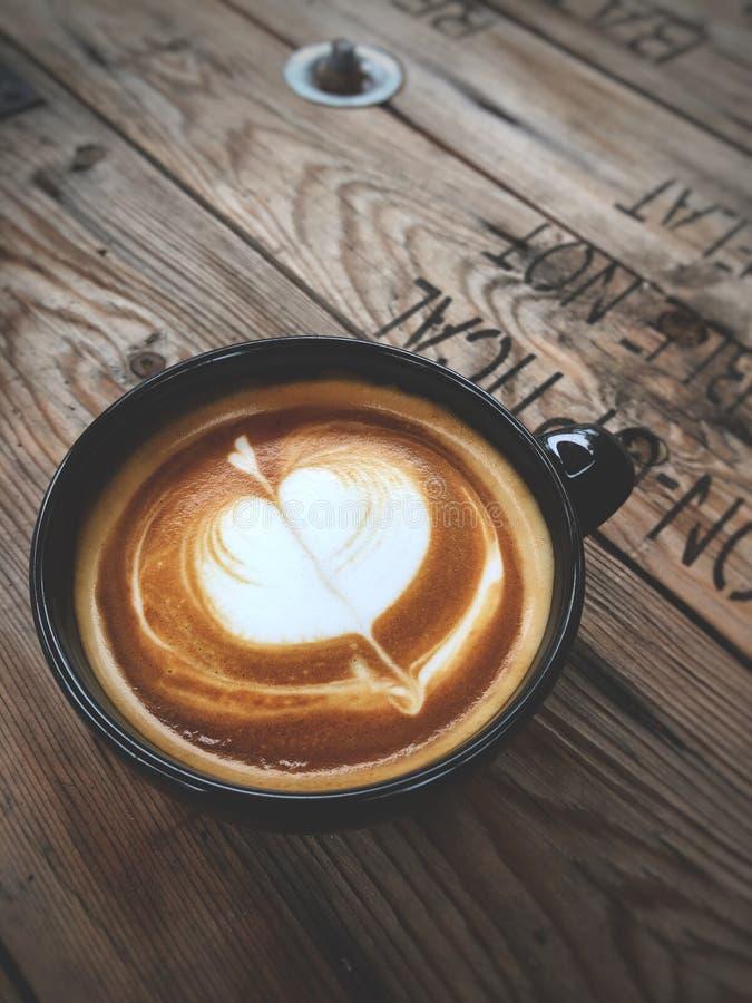 Café del arte del Latte del amor del corazón en taza negra en la tabla de madera del vintage Amante del caf? fotos de archivo