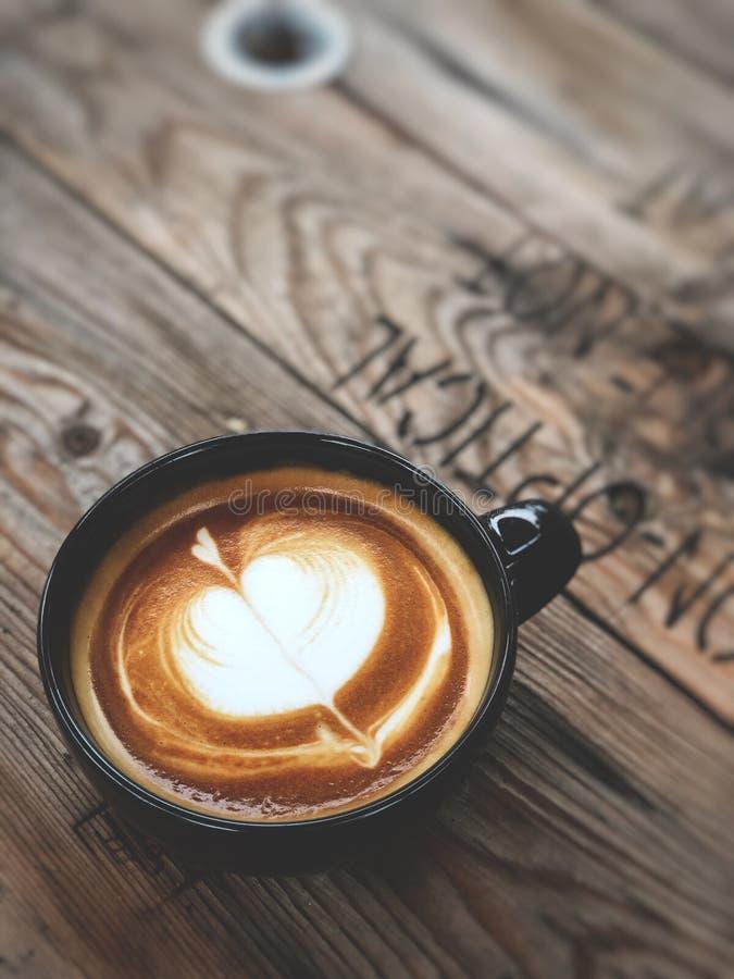 Café del arte del Latte del amor del corazón en taza negra en la tabla de madera del vintage Amante del caf? imagen de archivo