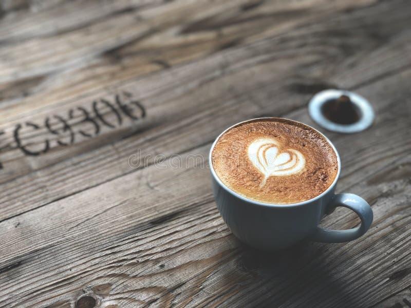 Café del arte del Latte del amor del corazón en taza negra en la tabla de madera del vintage foto de archivo libre de regalías