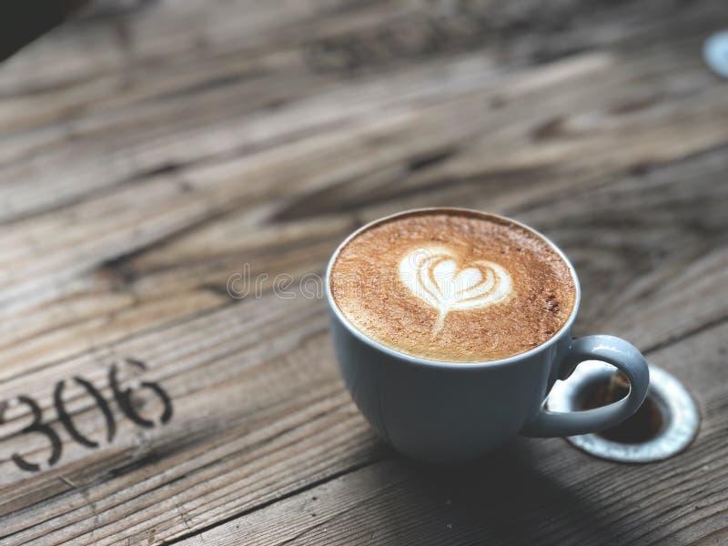 Café del arte del Latte del amor del corazón en taza negra en la tabla de madera del vintage fotografía de archivo libre de regalías