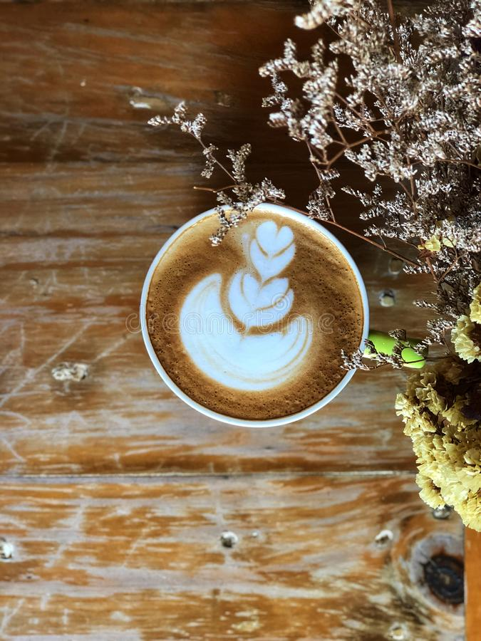 Café del arte del latte del corazón en la taza blanca en la tabla de madera del vintage y el primero plano secado de la flor foto de archivo libre de regalías