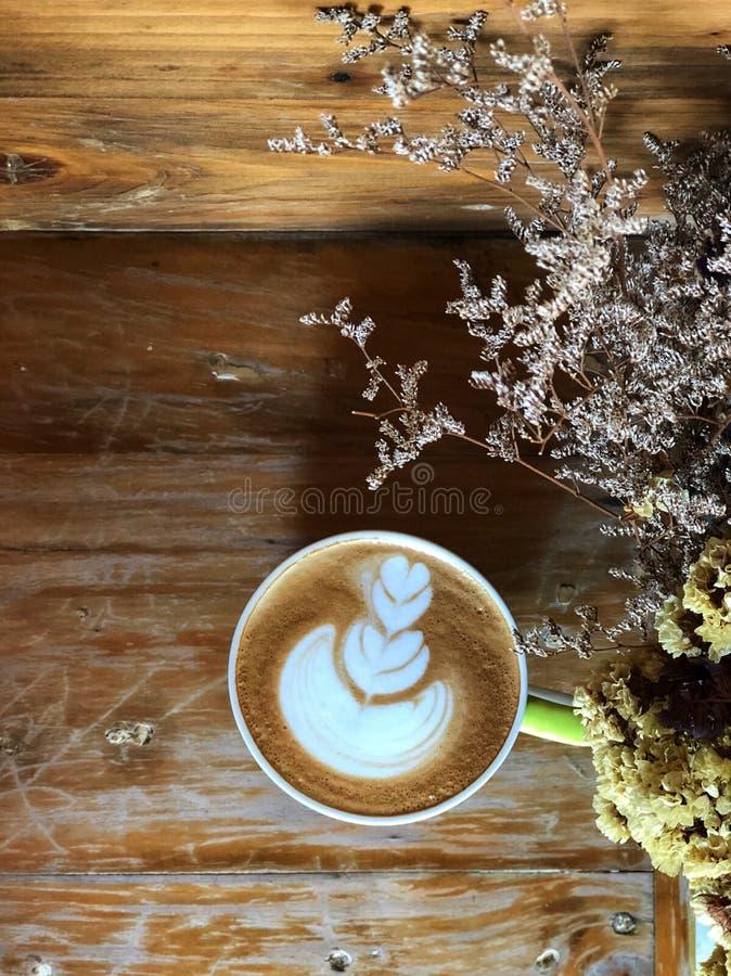 Café del arte del latte del corazón en la taza blanca en la tabla de madera del vintage y el primero plano secado de la flor imagenes de archivo