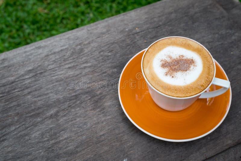 Café del capuchino en la taza blanca en la tabla de madera en jardín fotografía de archivo