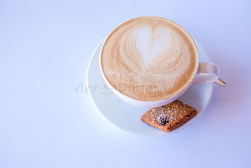 Café del capuchino o del latte en taza con leche y galletas espumejeadas Taza de café con biscotti de la almendra en el fondo bla foto de archivo libre de regalías