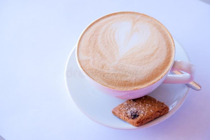 Café del capuchino o del latte en taza con leche y galletas espumejeadas Taza de café con biscotti de la almendra en el fondo bla fotos de archivo libres de regalías