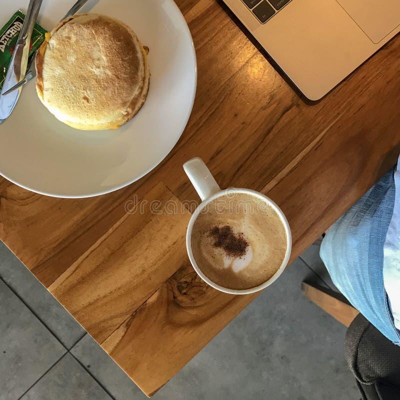 Café del capuchino y pan del bollo de la carne de vaca para el desayuno foto de archivo