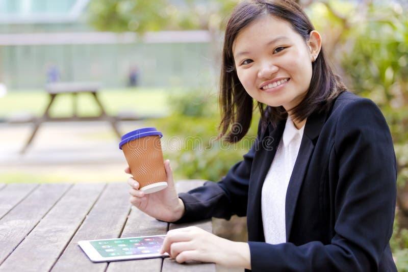 Café del ejecutivo de sexo femenino asiático joven y tableta de consumición con fotos de archivo