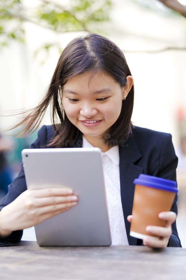 Café del ejecutivo de sexo femenino asiático joven y tableta de consumición con fotografía de archivo