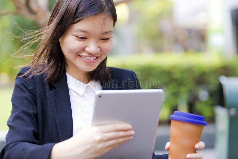 Café del ejecutivo de sexo femenino asiático joven y tableta de consumición con fotografía de archivo libre de regalías