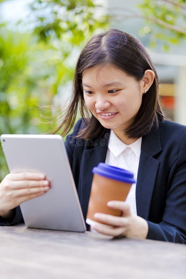 Café del ejecutivo de sexo femenino asiático joven y tableta de consumición con fotos de archivo libres de regalías