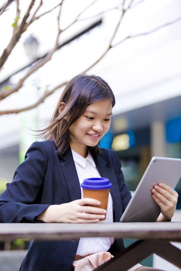 Café del ejecutivo de sexo femenino asiático joven y tableta de consumición con imagen de archivo libre de regalías
