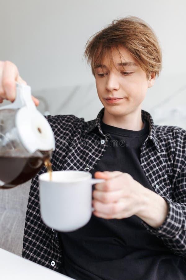 Café del hombre soñoliento joven que se sienta y de colada en cocina en casa fotos de archivo