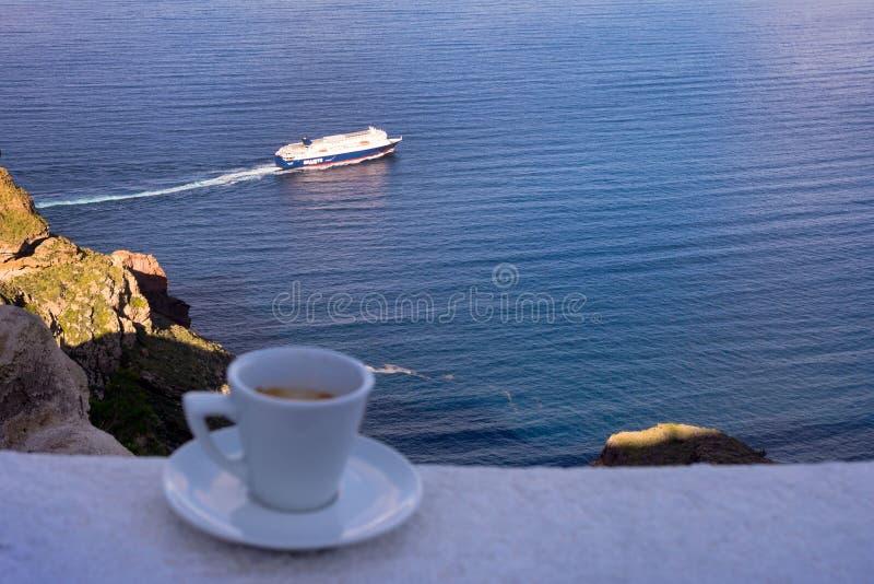 Café delicioso forte em um copo branco com uns pires contra o contexto do mar e de um forro de flutuação Grande come?o ao dia foto de stock