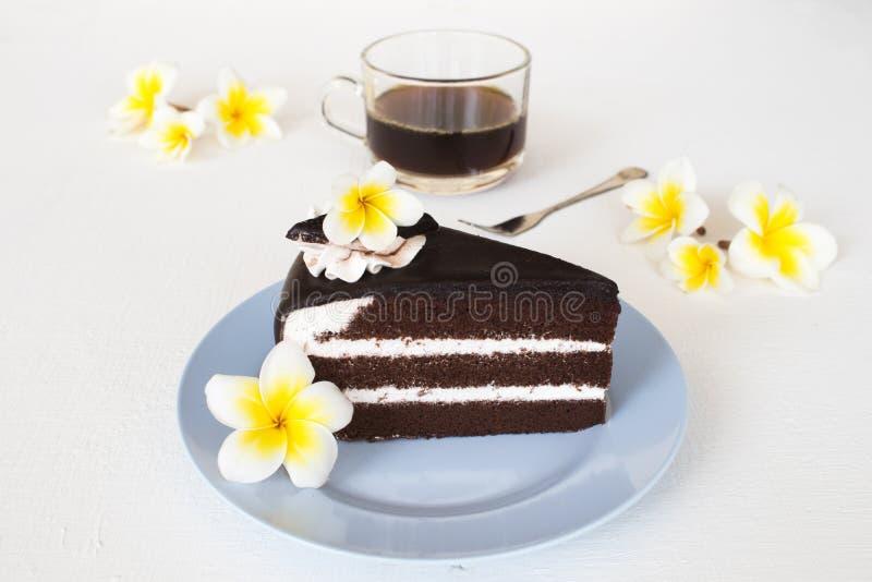 Café delicioso y caliente de la torta de chocolate del bocado del postre con el frangipani de la flor imágenes de archivo libres de regalías