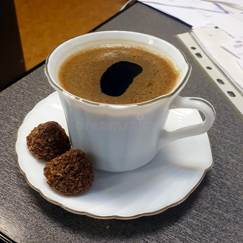 Café do cappuccino na tabela com os dois doces na placa imagem de stock