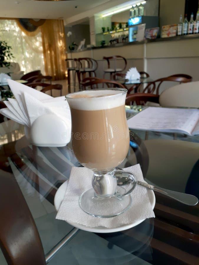 Café do cappuccino na tabela com vidros pretos imagens de stock