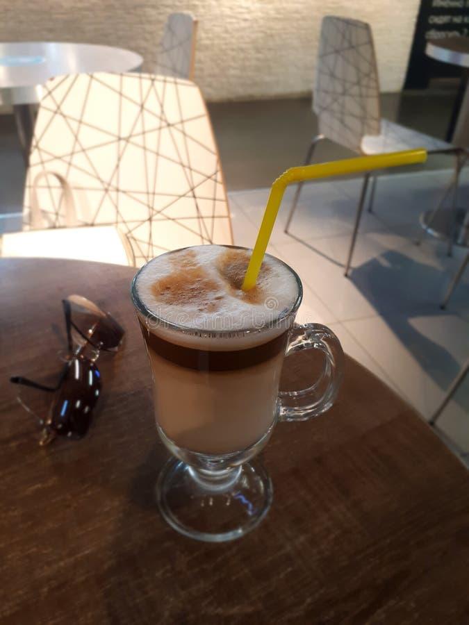 Café do cappuccino na tabela com vidros pretos imagens de stock royalty free