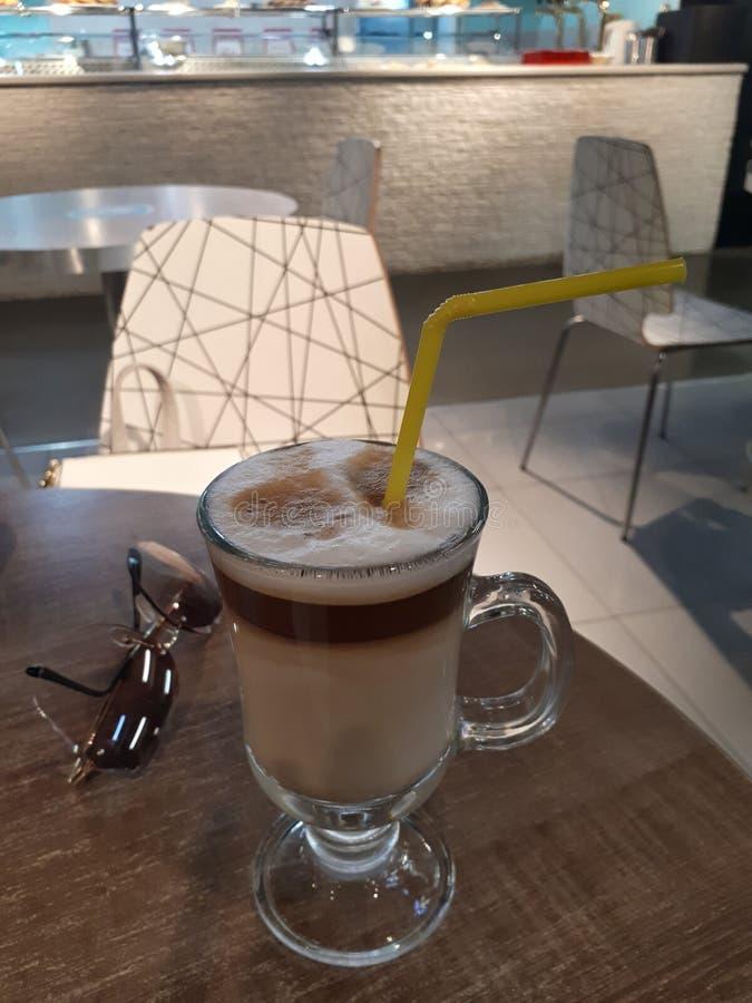Café do cappuccino na tabela com vidros pretos imagem de stock royalty free