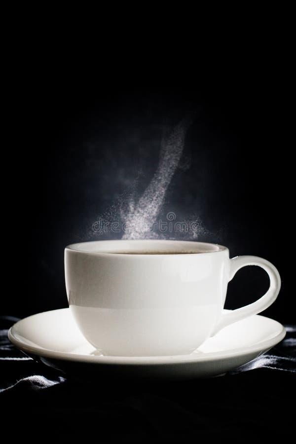 Café do copo branco com fumo no fundo preto imagem de stock
