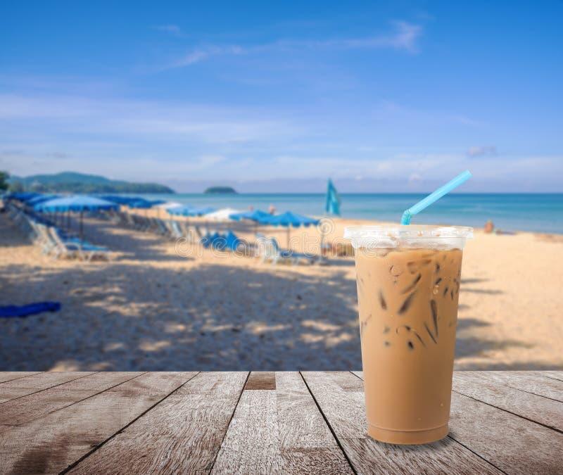 Café do leite de gelo com a areia borrada da praia e o céu azul do mar e o azul foto de stock