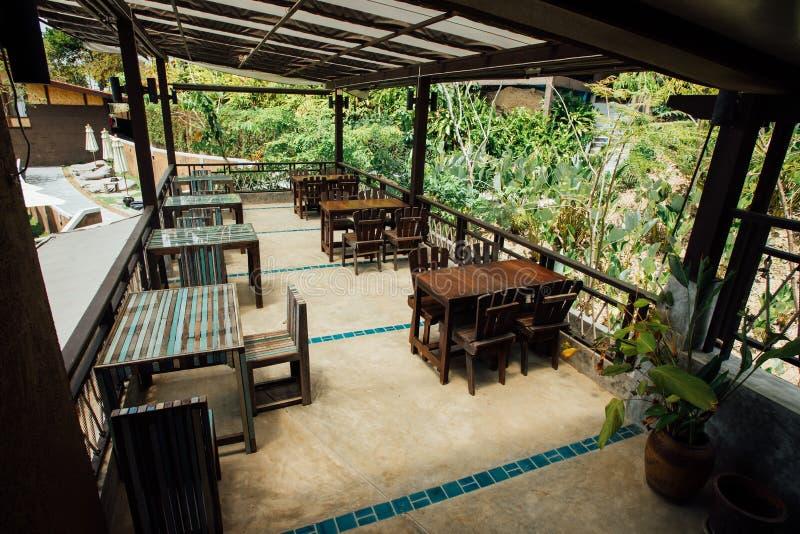 Café do verão no ar livre com mobília de madeira do vintage no jardim do verde do fundo fotografia de stock royalty free
