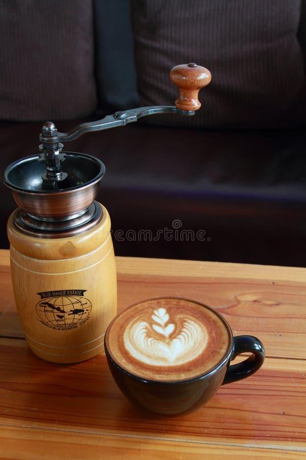 Café do vintage e moedor de café marrons na tabela de madeira do ouro fotografia de stock royalty free