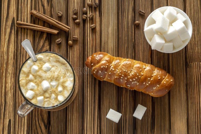 Café doux avec les guimauves et le petit pain de cannelle et de saucisse avec le sésame photo libre de droits