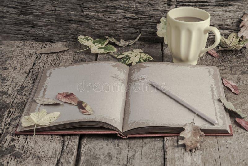 Café e caderno na tabela de madeira decorada com folhas de outono fotografia de stock