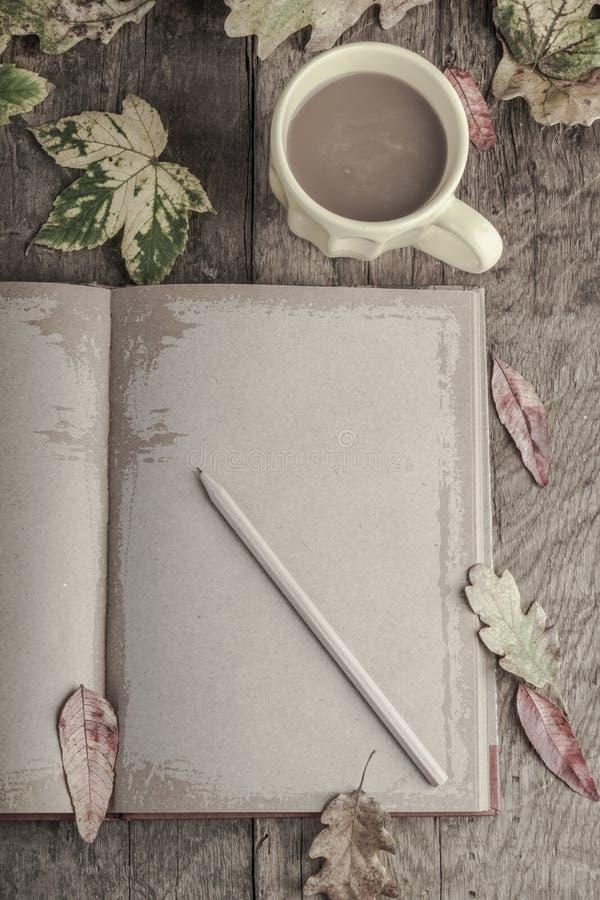 Café e caderno na tabela de madeira decorada com folhas de outono foto de stock royalty free