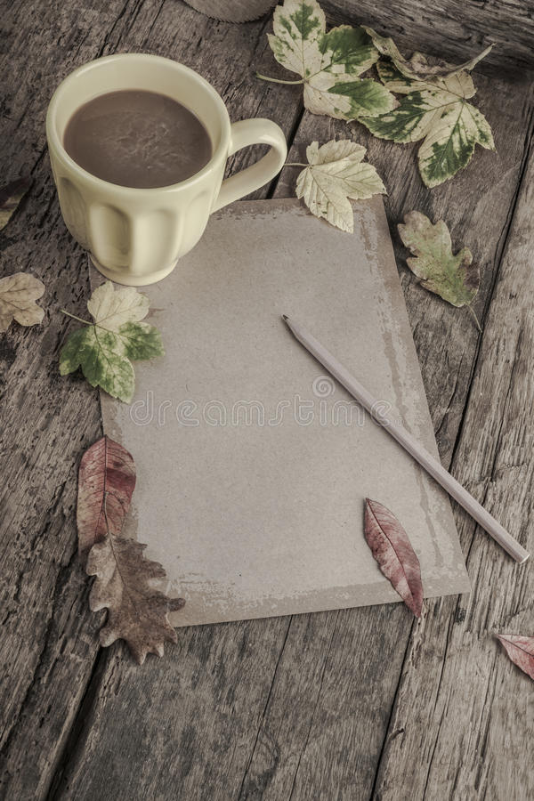 Café e caderno na tabela de madeira decorada com folhas de outono imagens de stock