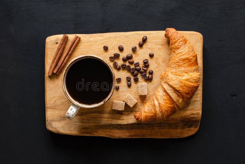 Café e croissant na placa de madeira, vista superior imagens de stock royalty free