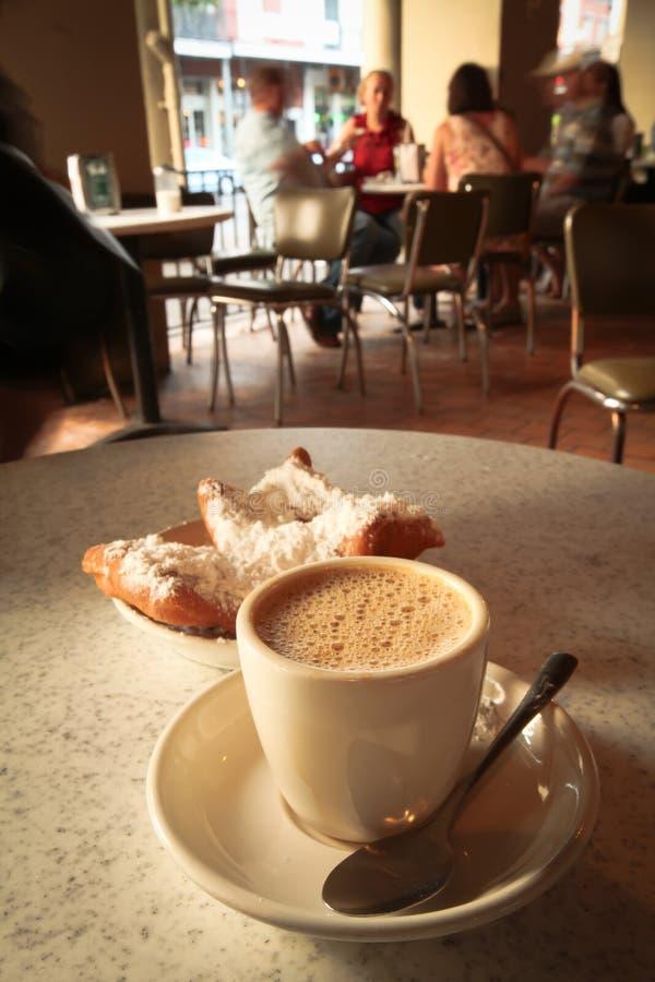 Café e filhóses de Beignet fotografia de stock