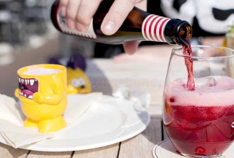 Café e luz solar Um vidro da cerveja belga do fruto Álcool na tabela A cerveja está derramando de uma garrafa Copie o espaço imagem de stock royalty free