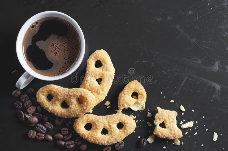 Café e pretzeis com açúcar no preto fotos de stock royalty free