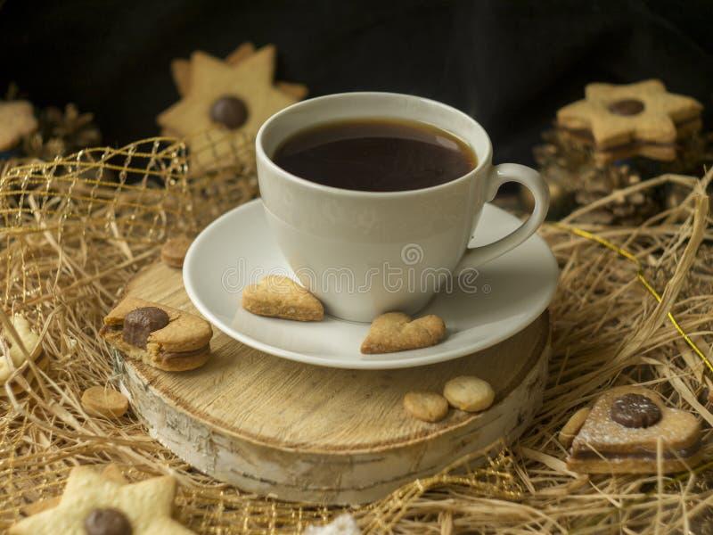 Café e uma cookie dada forma coração em uma serra de madeira em um fundo preto Café da manhã para ela no dia de Valentim Cookies foto de stock