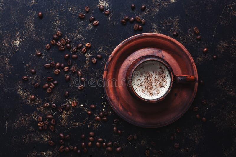 Café em um copo cerâmico marrom do vintage em um fundo escuro do grunge com os feijões de café roasted Vista superior, espaço da  fotografia de stock royalty free