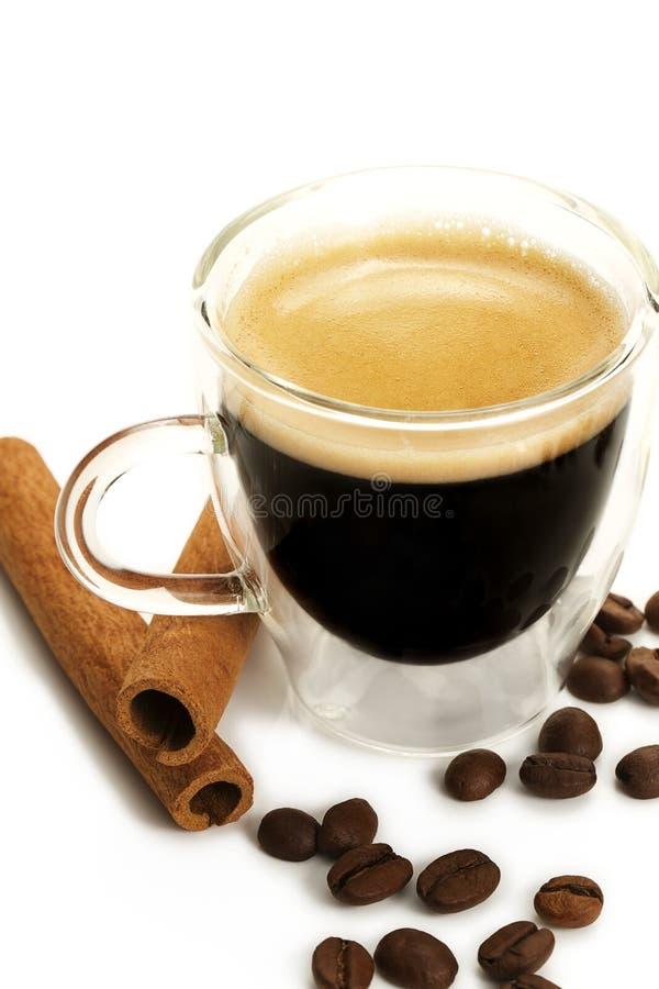 Café em um copo de vidro com canela e feijões imagem de stock
