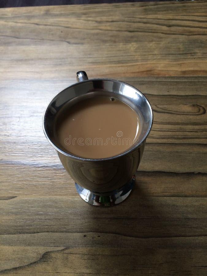 Café em uma tabela de aço inoxidável da madeira do copo fotos de stock royalty free