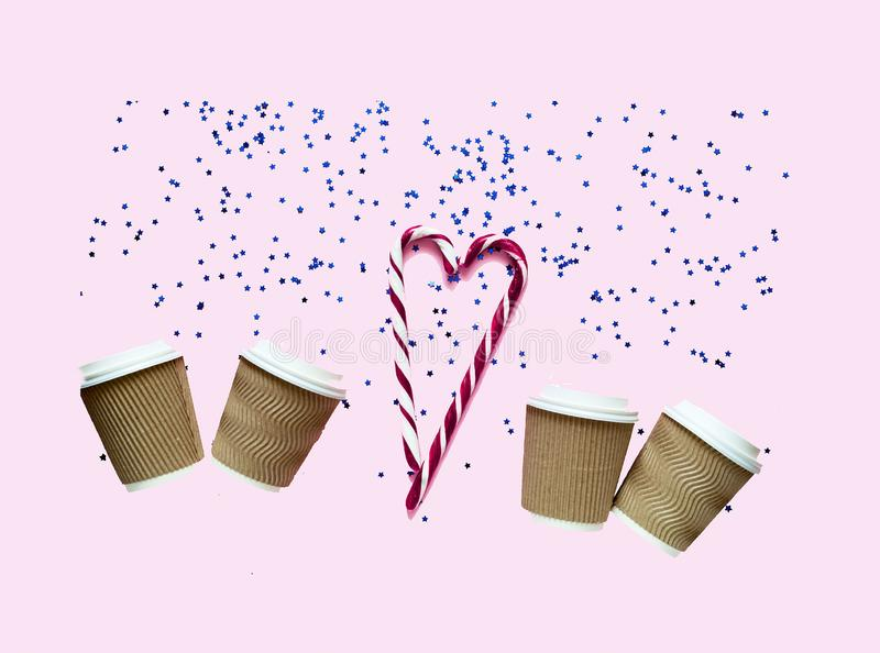 Café em uns copos de papel descartáveis no fundo na moda pastel do rosa com sparkles imagem de stock