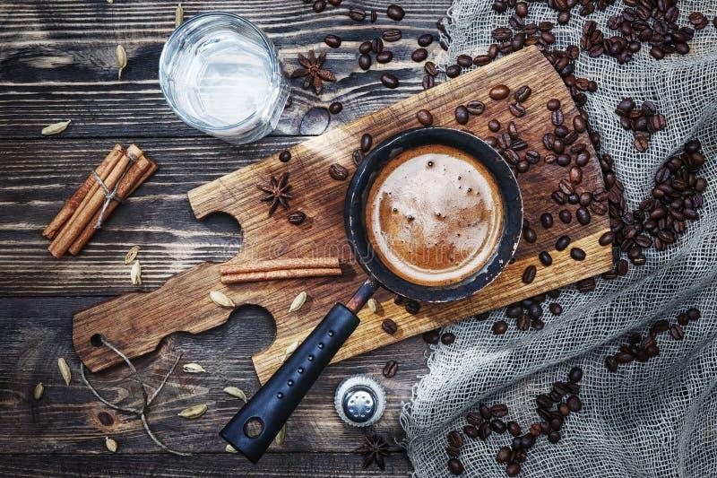 Café en cezve en una tabla de madera rústica con los granos de las especias, del canela, del agua, de la sal y de café cerca de l imagen de archivo libre de regalías