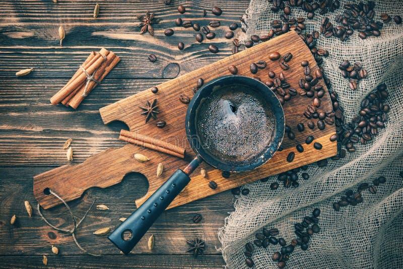 Café en cezve en una tabla de madera rústica con los granos de las especias, del canela y de café Mirada de la cámara entonado imagenes de archivo