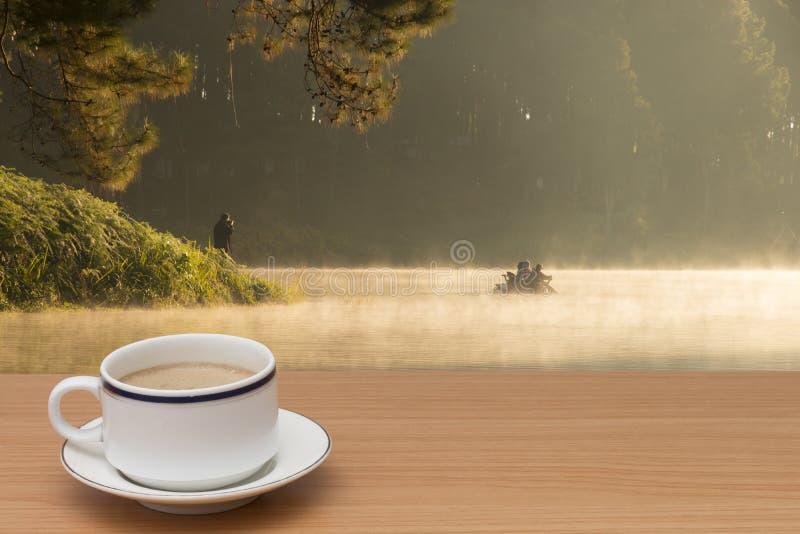 Café en la tabla de madera con paisaje hermoso imágenes de archivo libres de regalías