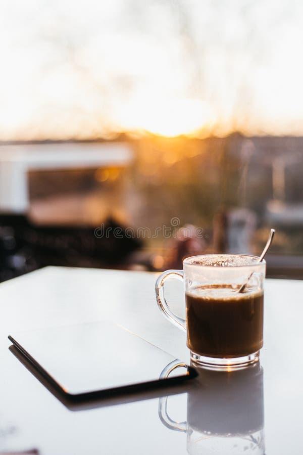 Café en la tabla y la luz del sol imagen de archivo libre de regalías