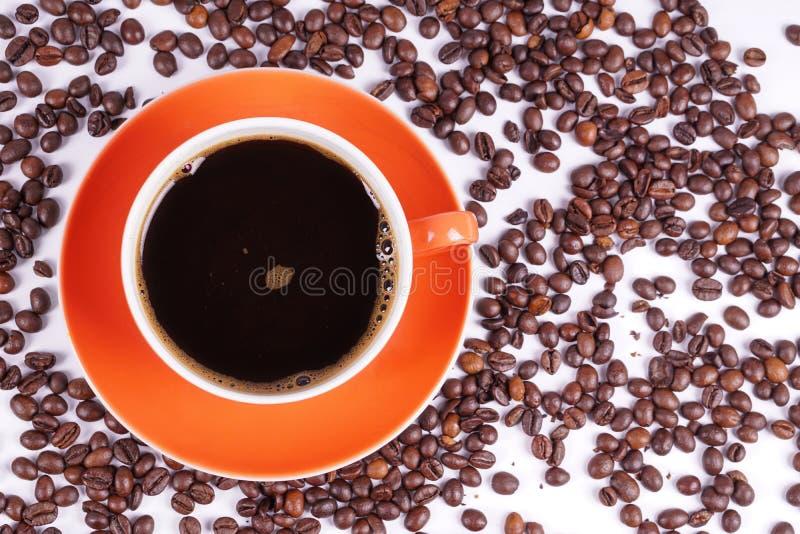 Café en la taza anaranjada rodeada con los granos de café fotografía de archivo libre de regalías