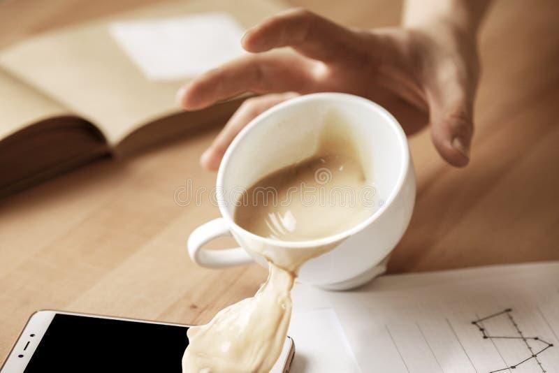 Café en la taza blanca que se derrama en la tabla en el día laborable de la mañana en la tabla de la oficina foto de archivo libre de regalías