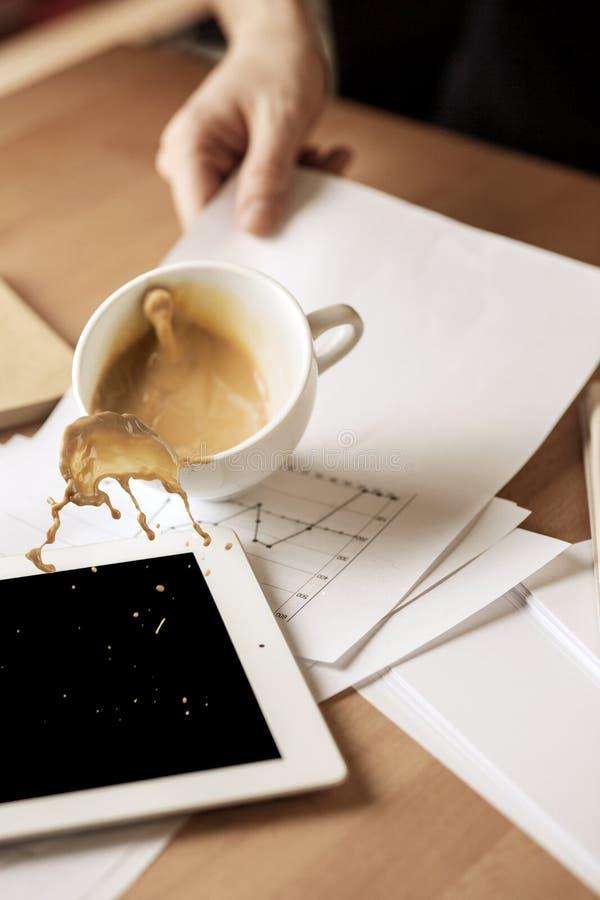 Café en la taza blanca que se derrama en la tabla en el día laborable de la mañana en la tabla de la oficina imagenes de archivo