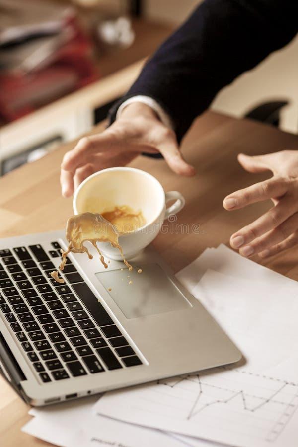 Café en la taza blanca que se derrama en la tabla en el día laborable de la mañana en la tabla de la oficina fotografía de archivo