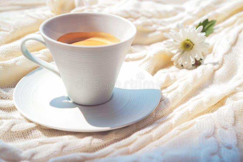 Café en la taza blanca y la flor blanca agradable en la tela escocesa suave en luz del sol suave de la mañana fotos de archivo libres de regalías
